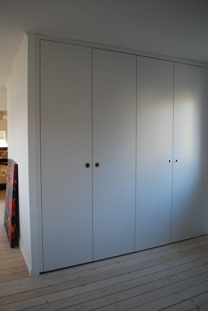 Platsbyggd garderob med vitlackerade luckor